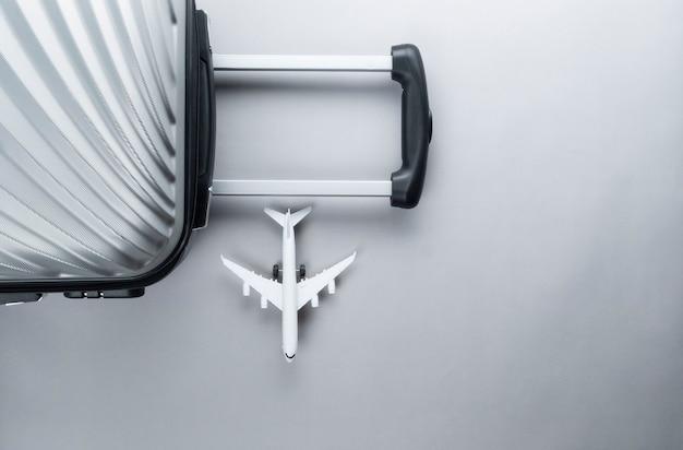 Valigia grigia piatta con mini aereo. concetto di viaggio
