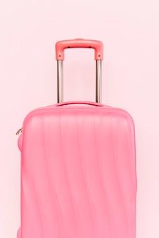 Valigia rosa per viaggiare su sfondo rosa