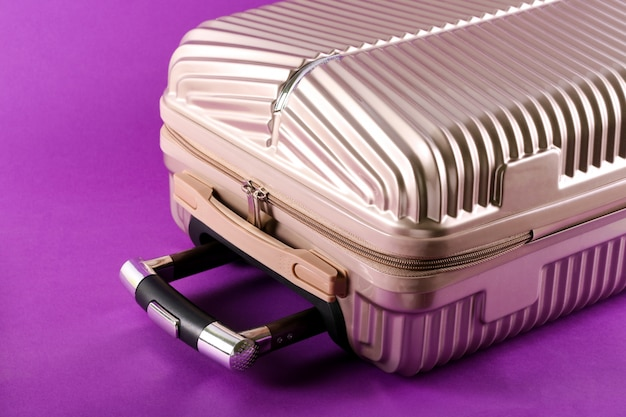 Valigia su sfondo viola? concetto di viaggio e vacanza