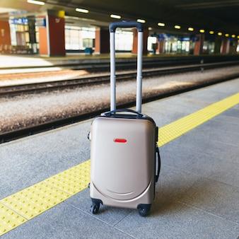 Valigia sulla piattaforma della stazione ferroviaria