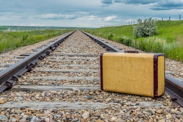 Valigia vintage in mezzo ai binari della ferrovia nelle praterie