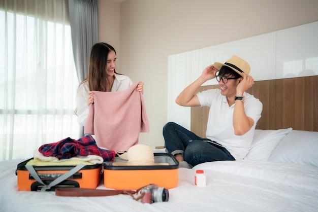 Valigie asiatiche dell'imballaggio del viaggiatore delle coppie di felicità che preparano per la vacanza di viaggio insieme e che sembrano divertenti quando si preparano al viaggio. concetto asiatico di stile di vita di viaggio di viaggiatore con zaino e sacco a pelo.