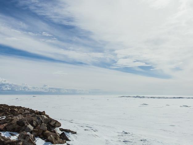 Valle coperta di neve in una fredda giornata invernale sotto il cielo nuvoloso luminoso