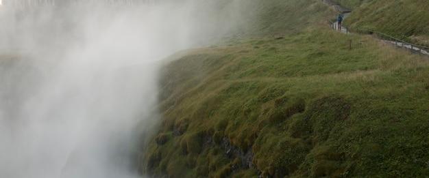 Valle nebbiosa accanto al sentiero escursionistico verdeggiante