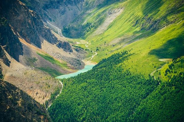 Valle panoramica con un bellissimo lago di montagna, boschi di conifere e montagne rocciose.