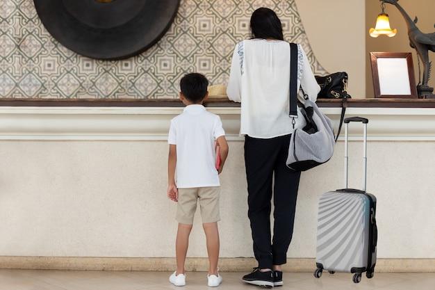 Valore di famiglia madre e figlio che registrano all'hotel con la valigia