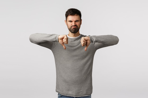 Valutazione, opinione dei clienti e concetto di emozioni. uomo barbuto adulto arrabbiato e deluso scocciato e infastidito in maglione grigio, che fa smorfie con espressione odiosa, mostra il pollice verso il basso, non piace il gesto