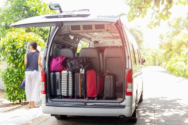 Van con bagagli su un sabbioso con la donna nel concetto di viaggio del backgroung della sfuocatura.