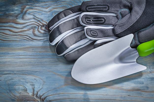 Vanga della mano dei guanti protettivi sul concetto di giardinaggio del bordo di legno