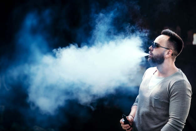 Vaper con la barba in occhiali da sole vaping all'aperto