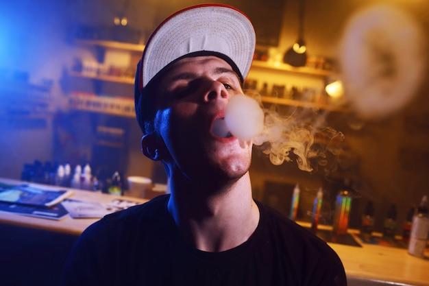 Vaping man holding a mod. una nuvola di vapore nel negozio di vaporizzatori.