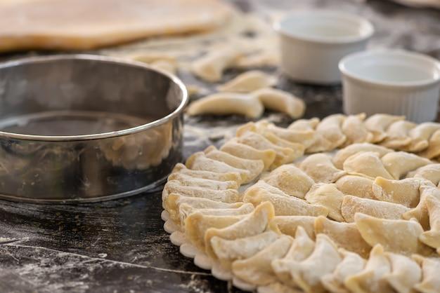 Vareniki sul taglio della tavola di legno con farina.
