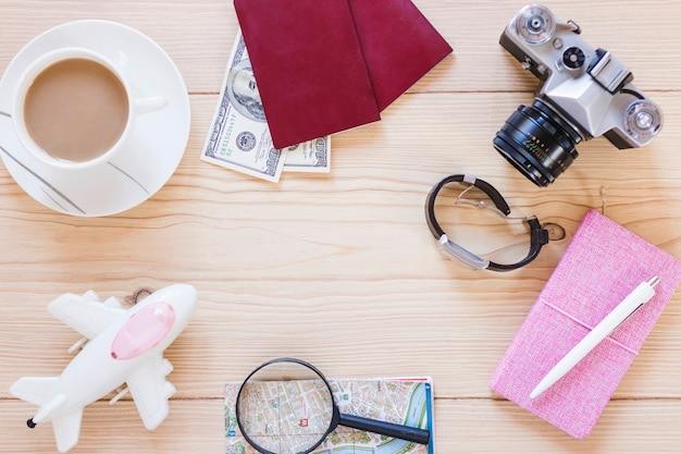 Vari accessori del viaggiatore con la tazza di tè su fondo di legno