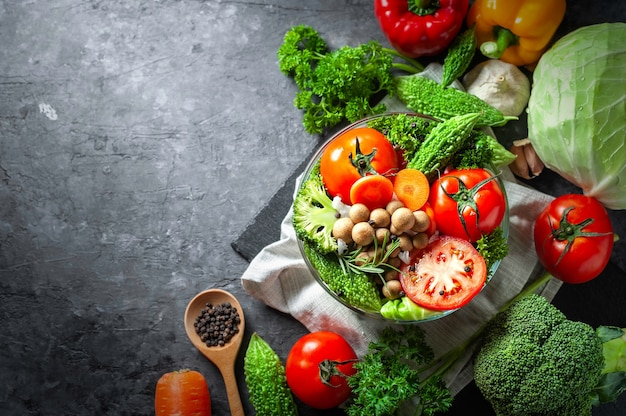 Vari alimenti biologici di verdure fresche per sano su fondo rustico scuro con copia spac