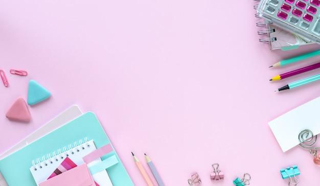 Vari articoli di cancelleria colorati per la scuola e l'ufficio su sfondo rosa con copyspace.