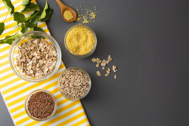 Vari cereali non cotti. diversi tipi di semole in ciotole su sfondo grigio.
