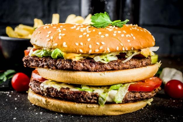 Vari cibi per feste, hamburger, patatine fritte, patatine fritte, cetrioli sottaceto, cipolle, pomodori e bottiglie di birra fredda
