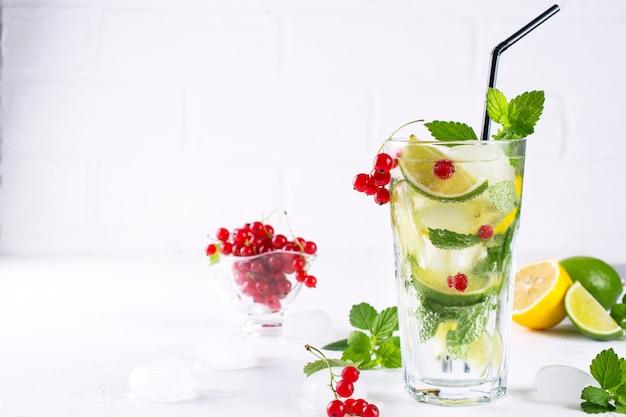 Vari cocktail di limonata o mojito ai frutti di bosco, lime al limone fresco ghiacciato, acqua infusa di ribes rosso, bevande disintossicanti salutari estive sfondo chiaro copia spazio