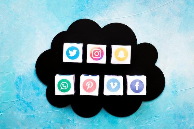 Vari contenitori di icone di social media su nuvola nera su sfondo blu