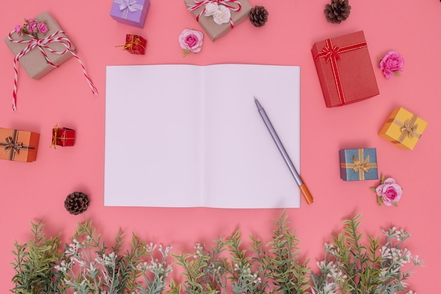 Vari contenitori di regalo e piante verdi intorno all'immagine e al libro bianco