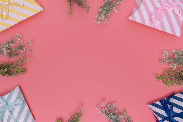 Vari contenitori di regalo su fondo rosa