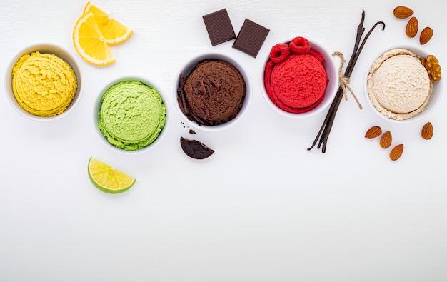 Vari di gelato sapore palla mirtillo, lime, pistacchio, mandorla, arancia, cioccolato e vaniglia istituito su fondo di legno bianco. concetto di menu estate e dolce.