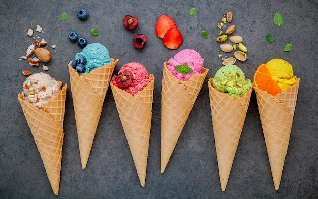 Vari di sapore di gelato in configurazione di coni su sfondo di pietra per il menu di dolci.
