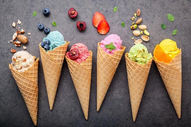 Vari di sapore di gelato in configurazione di coni su sfondo di pietra scura.