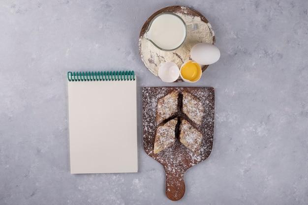 Vari dolci e ingredienti sul piatto di legno con un taccuino a parte