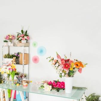 Vari fiori freschi sullo scrittorio di vetro in negozio floreale