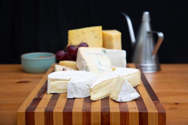 Vari formaggi che pongono sul bordo di legno