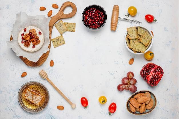 Vari formaggi e piatto di formaggi sul tavolo luminoso con diversi tipi di noci e frutta