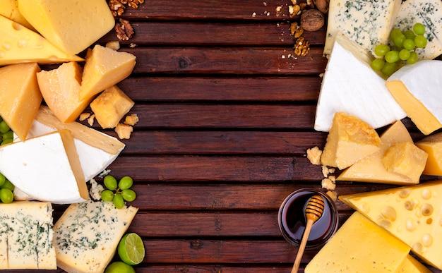Vari formaggi su tavola di legno con spazio vuoto.