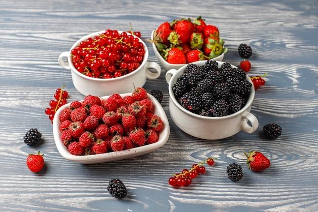 Vari frutti di bosco freschi estivi, mirtilli, ribes rosso, fragole, more, vista dall'alto.