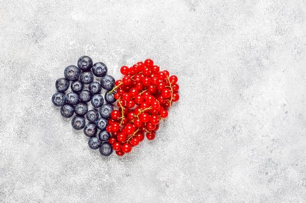 Vari frutti di bosco freschi estivi, mirtilli, ribes rosso, vista dall'alto.