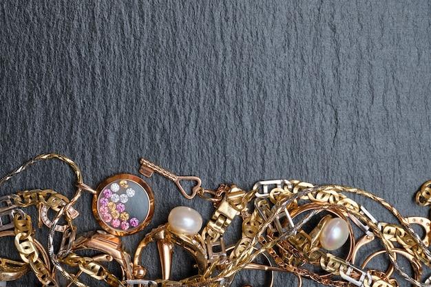 Vari gioielli, anelli, catene su pietra nera. vista dall'alto. copia spazio.