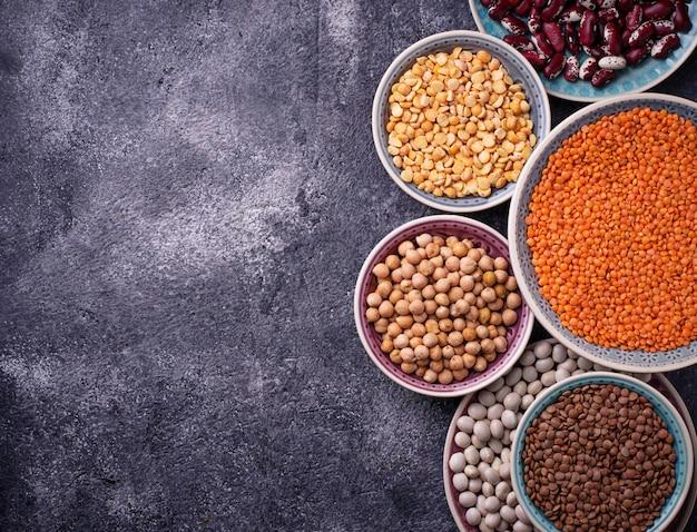 Vari legumi ceci, lenticchie rosse, lenticchie nere, piselli gialli e fagioli. messa a fuoco selettiva superiore