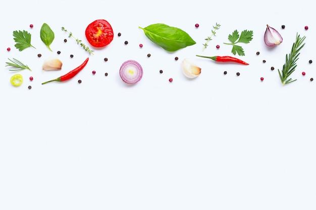 Vari ortaggi freschi ed erbe su fondo bianco