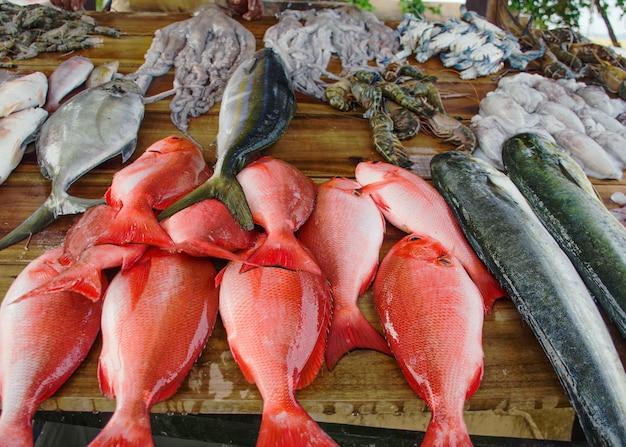 Vari pesci appena pescati sul bancone in legno. mercato di strada ai asia.