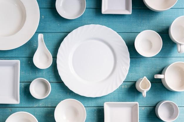 Vari piatti e ciotole bianchi vuoti su backgroun di legno
