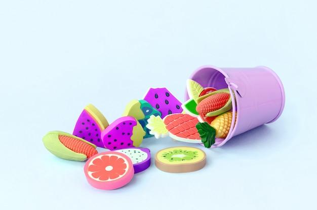 Vari piccoli frutti freschi vengono versati da un piccolo secchio viola