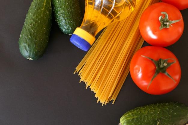 Vari prodotti. spaghetti, pasta, pomodori, cetrioli e olio di girasole vegetale.