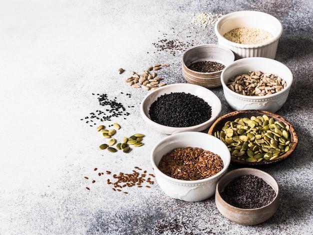 Vari semi - sesamo, semi di lino, semi di girasole, semi di zucca, papavero, chia in ciotole su uno sfondo grigio.