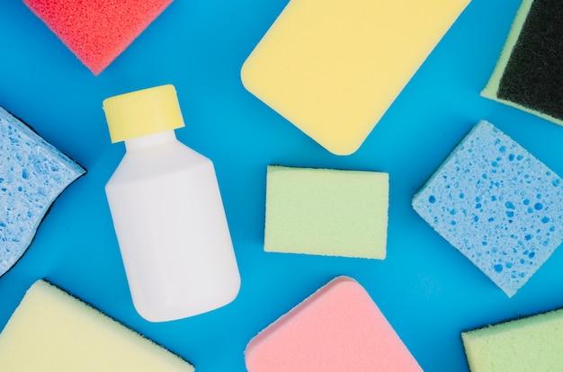 Vari spugna colorata con bottiglia su sfondo blu