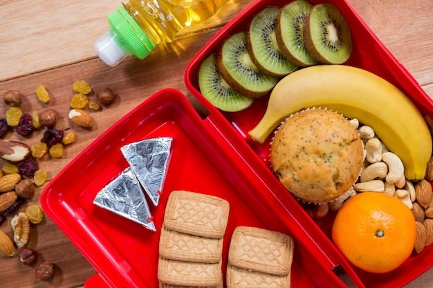Vari spuntino, frutta e olio su tavola di legno