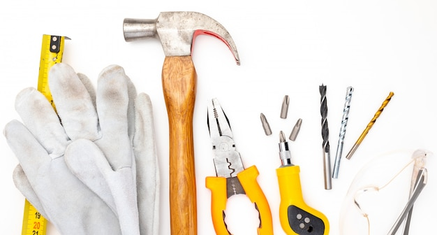 Vari strumenti di costruzione. isolato. martello fai-da-te fatto in casa, guanti e occhiali di sicurezza, metro, pinze, cacciavite, punte.