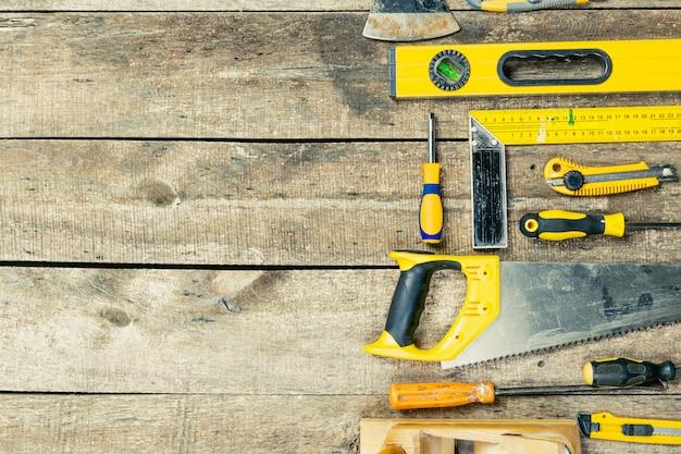 Vari strumenti di costruzione messi sul bordo di legno