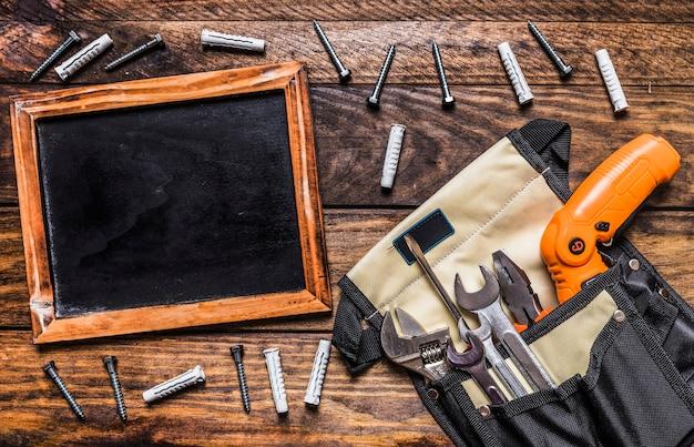 Vari strumenti nella borsa per utensili vicino all'ardesia e ai bulloni in bianco su fondo di legno