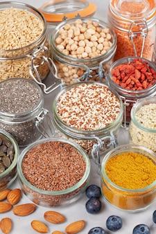 Vari supercibi bacche di goji, quinoa, chia, semi di canapa, semi di lino, ceci, avena, mandorla, mirtilli, curcuma, matcha e lenticchie. concetto vegano e vegetariano dei prodotti biologici di dieta sana di cibo