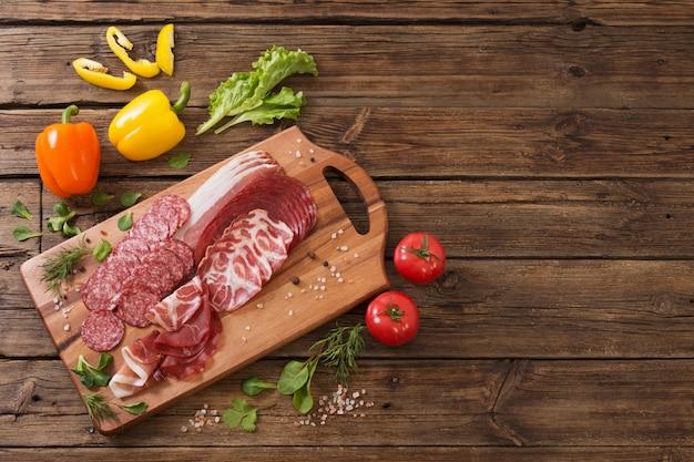 Vari tipi di carne e verdure sulla tavola di legno